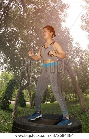 A Beautiful Asian Woman, Aged 20-30, Is Exercising By Jumping On Tires In The Park.