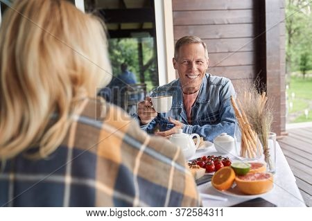 Smiling Mature Man Eating Meals With Woman On Wooden Terrace