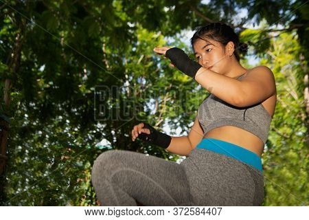 Beautiful Young Asian Woman 20-30 Year Old Posing With Black Boxing Gloves Punching In The Park.