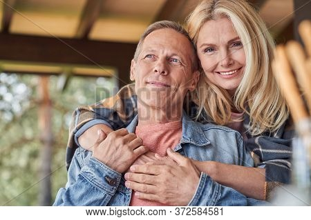 Smiling Mature Woman Hugging Husband In Open Terrace