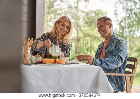 Happy Mature Spouses Having Tea With Toasts