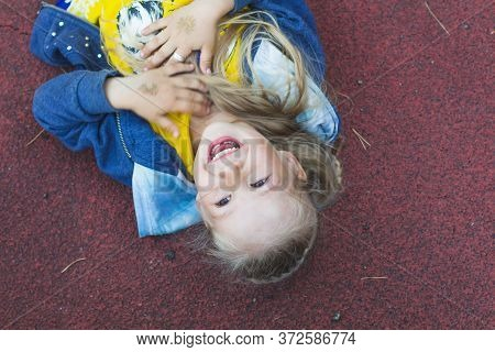 Caucasian Girl With Long Hair Lies On The Playground, Hugs Her Hands To Her Chest And Laughs.the Mil