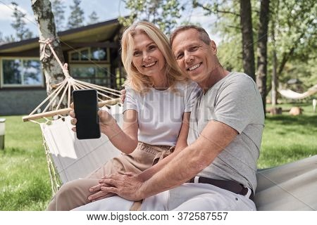 Jolly Mature Spouses With Smartphone Outside Countryside Villa