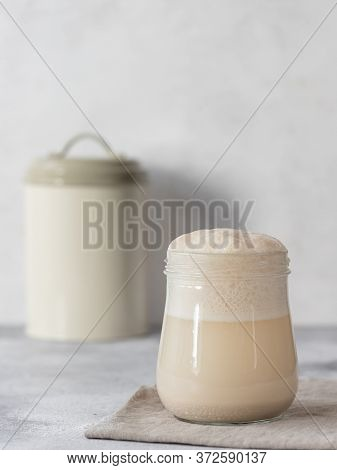 Heaping Jar Of Sourdough Starter Yeast, A Container With Flour In The Background. Vertical Image. Gr