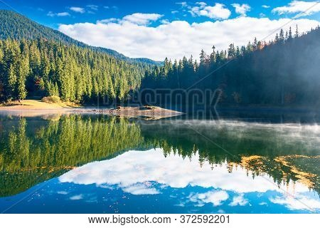 Lake Landscape At Foggy Sunrise. Misty Scenery Reflecting In The Water. Wonderful Autumn Morning In