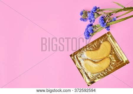 Golden Flakes Under The Eyes With Purple Flowers On A Pink Background With Copy Space. Anti Ages Cos