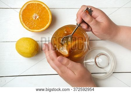 Teenagers Hands Holding A Spoon With Orange And Lemon Jam. Homemade Orange Marmalade. Breakfast In R