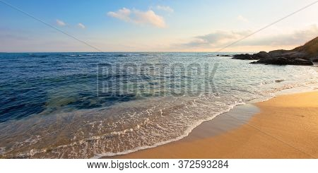 Sunrise On The Beach. Rocks On The Sandy Shore. Sunny Weather With Some Clouds. Calm Seascape In The