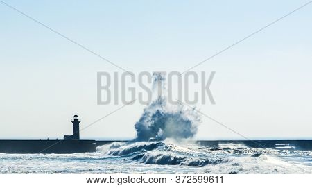 Sea Wave Hits An Underwater Rock And Creates A Plume Hitting A Lighthouse In Porto, Portugal