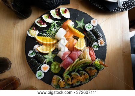 Delicious Various Japenese Sushi Rolls On A Slate Plate In A Restaurant