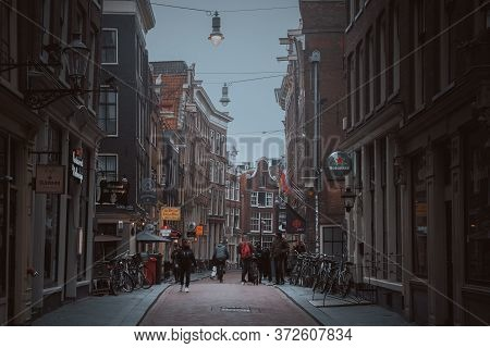 Amsterdam, Netherlands - March 5, 2020: People Are Walking On The Street In Amsterdam City Center Ol