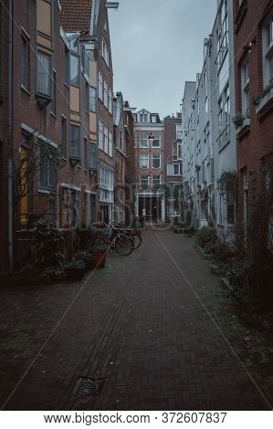 Amsterdam, Netherlands - March 5, 2020: Empty Narrow Street With Residential Houses In Amsterdam Cit