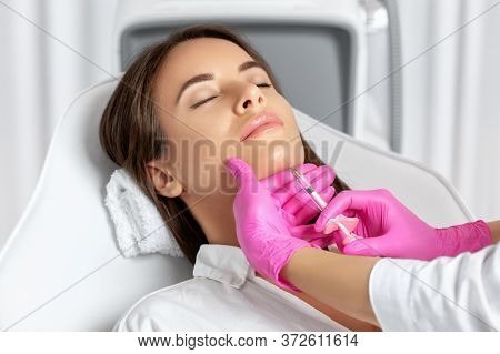 Beautiful Brunette Woman At The Beautician.cosmetologist Does Anti Wrinkle Injections On The Chin Ag