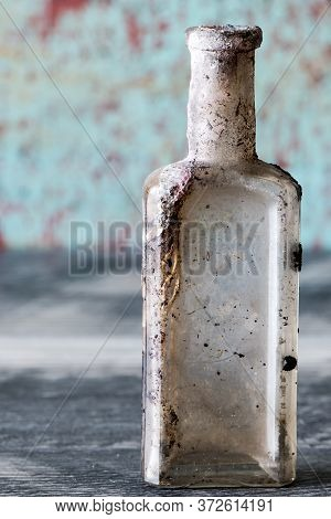 Vintage Oil And Tincture Glass Bottle Weathered On Grungy Background.  Old Bottle With Calcium Depos