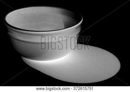 White Bowl. Ceramic Bowl. Artistic view of a white ceramic bowl with shadows. Isolated on white. Room for text. Clipping Path. Black & White negative effect.