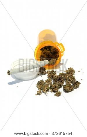 Prescription Marijuana. Cannabis Sativa in a plastic prescription bottle with a hand rolled Joint. Isolated on white.