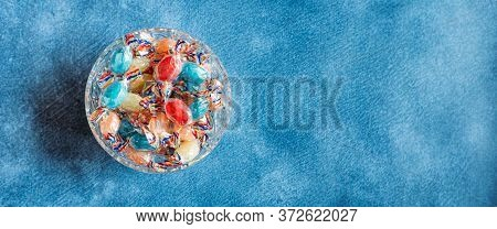 Bowl Full With Mix Hard Wrapped Candies Isolated On Blue Background. Space For Text