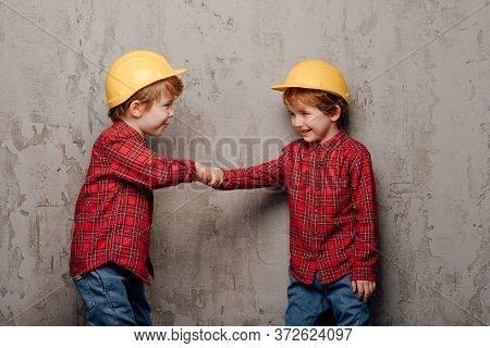 Cheerful Twin Brothers In Similar Checkered Shirts And Helmets Standing On Background Of Shabby Wall