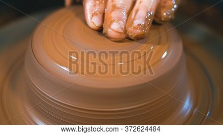 Pottery Concept. Professional Ceramist Working With Clay At Throwing Table In Workshop, Close Up.