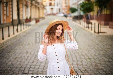 Portrait Cheerful Tourist Woman Walk On Ancient Street In Old Town. Attractive Woman In Straw Hat, W