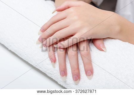 Woman Holds Hands On Towel For Manicure Treatment Procedure In Spa Salon. Beautiful Hands Of Young W