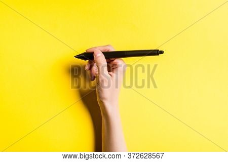 Cropped View Of Designer Holding Stylus Of Graphics Tablet On Yellow Background