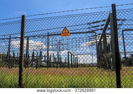 Sign Showing The Words High Voltage In German Language At The Fence Of A Big Substation Distributing