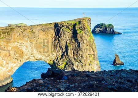 Travel to the fabulous island of Iceland. The southern edge of Iceland. Cape Dyrholaey. Giant rock ledge - arch. Volcanic cliffs above a black sand beach