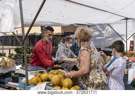 Calvià, Mallorca, Spain - June 15 2020: Older Woman With Face Mask Paying The Vendor At A Fruit Stal