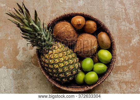 Top View Of Ripe Exotic Fruits In Wicker Basket On Weathered Surface