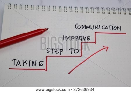Taking Step To Improve Communication Write On A Book Isolated On Wooden Table.
