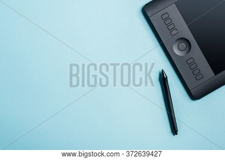 Top View Of Stylus Near Drawing Pad On Blue Background With Copy Space