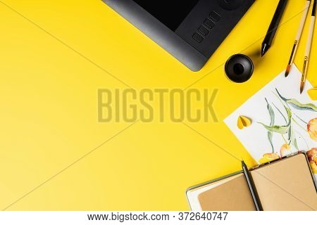 Top View Of Paintbrushes Near Painting, Drawing Tablet, Notebook And Stylus On Yellow