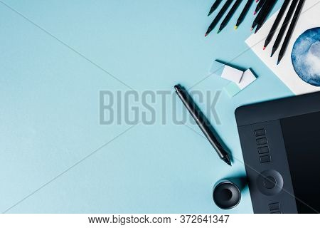 Top View Of Graphics Tablet With Stylus, Color Pencils And Watercolor Drawing On Blue Background