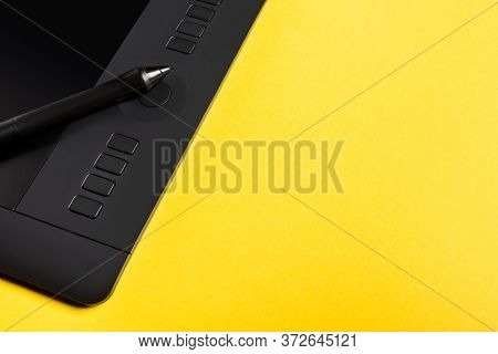 Close Up View Of Stylus On Graphics Tablet On Yellow Background