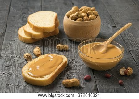 Peanut Paste With Bread And Peanut Fruit On A Wooden Table. Natural Peanut Cream.