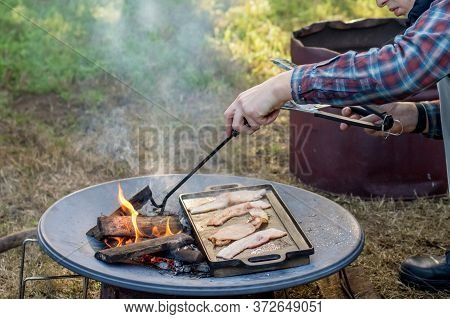 Breakfast Camp Cooking. Man Grilling Crispy Bacon On A Cast Iron Plate Over The Camp Fire
