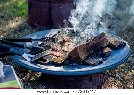 Breakfast Camp Cooking. Crispy Bacon On A Cast Iron Plate Over The Camp Fire