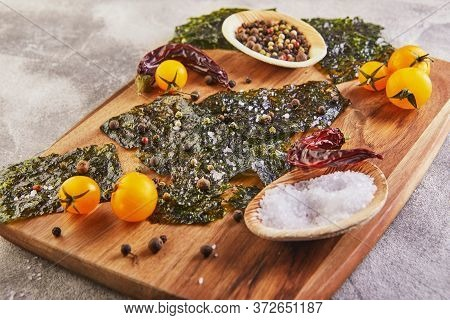 Crispy Nori Seaweed With Cherry Tomatoes And On A Wooden Board On Gray Concrete. Japanese Food Nori.