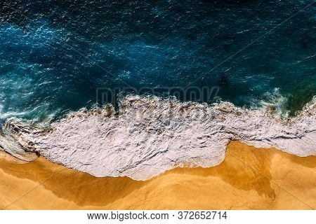 Beautiful Sandy Beach At Sunset. Beach With Yellow Sand And Sea Foam. The Sea Wave Covers The Sandy