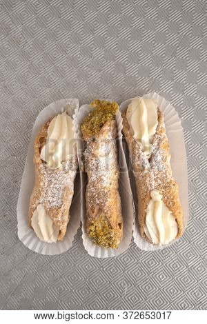 Top view of three cannoli freshly display in nice paper on a metal and textured background