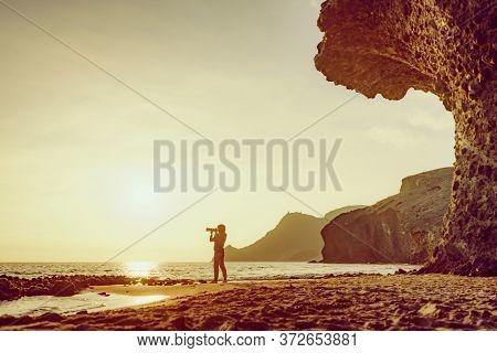 Tourist Woman With Camera Taking Travel Picture On Monsul Beach. Cabo De Gata Nijar Natural Park, Pr