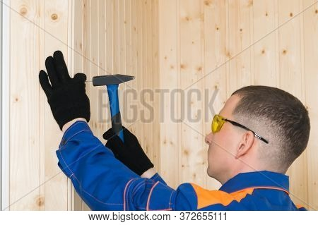Man In Construction Clothes And Goggles Nails The Board With Nails And A Hammer