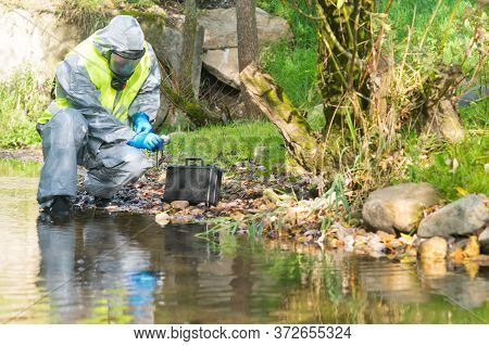 Environmental Pollution Scientist In Protective Suit Adjusts Rubber Glove While Sitting By The River