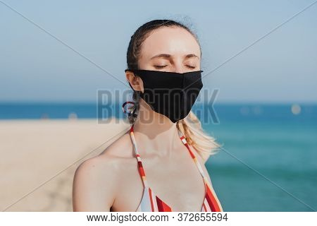 Portrait Of A Young Woman Wearing Reusable Protective Face Mask At The Beach. Face Protection From V