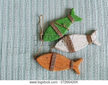 Three Wooden Decorative Fish Tied With Twine. Interior Items In Country Style. Creating Comfort Thro
