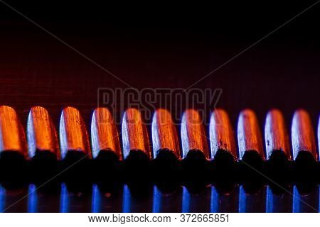 Edge Of An Illuminated  Serrated Knife And Their Reflection Macro Shot. Image Suitable As A Backgrou
