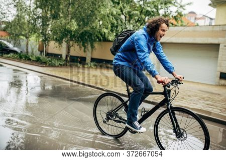 Horizontal Outdoor Image Of Handsome Man Cycling On His Bike Down The Street Next To The House. Cauc