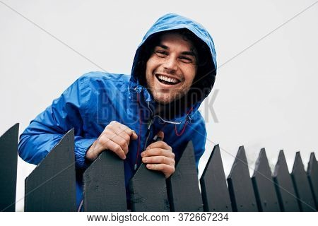 Outdoor Portrait Of Happy Man Wearing Blue Raincoat During Rain. Handsome Male In Blue Raincoat Enjo