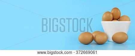 Fresh Chicken Eggs In White Bowl And Chicken Eggs On Blue Background With Copy Space. Uncooked Raw E